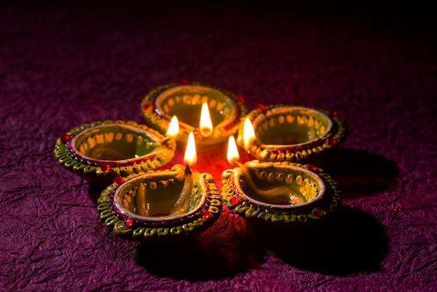 Lâmpadas de argila diya acesas durante a celebração de diwali. saudações cartão design indiano hindu light festival chamado diwali