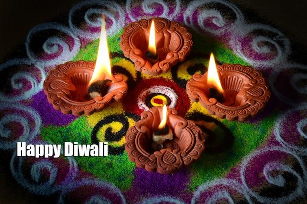 Lâmpadas de barro diya acesas durante a celebração do diwali, rangoli ao fundo