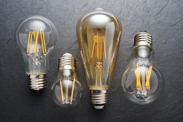 Lâmpadas de filamento de led transparentes modernas em fundo de ardósia preta