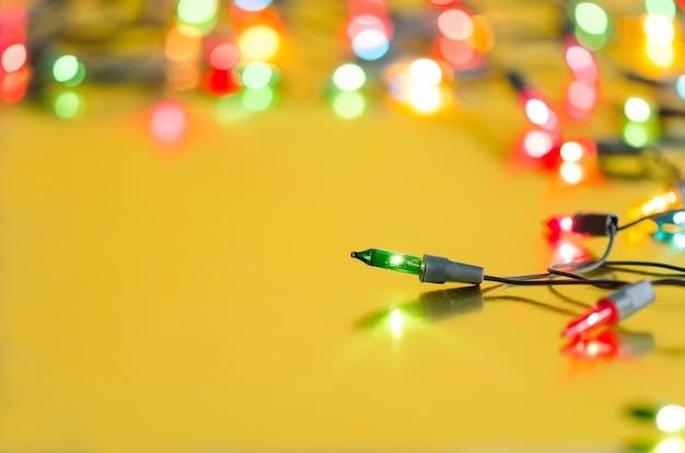 Lâmpadas de natal na seqüência em multi cores no espaço de fundo amarelo para a árvore de natal