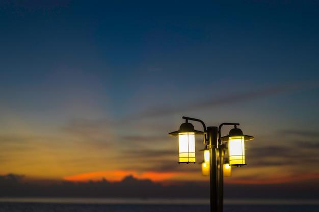 Lâmpadas de rua à noite. lâmpadas de rua brilhantemente iluminadas no por do sol.