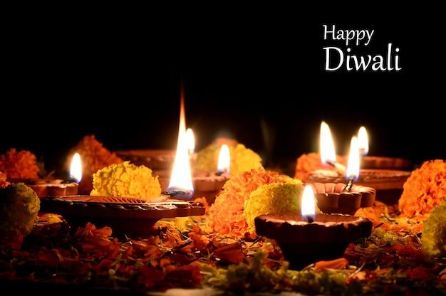 Lâmpadas diya de argila acesas durante a celebração do diwali. saudações festival hindu light festival indiano de design de cartão chamado diwali