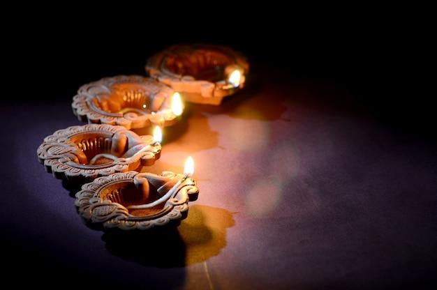 Lâmpadas diya de argila coloridas acesas durante a celebração de diwali. greetings card design festival indiano da luz hindu chamado diwali.