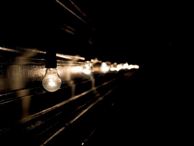 Lâmpadas em fundo preto. luz turva e bokeh. magia de ano novo e natal