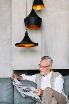 Lâmpadas iluminadas sobre o homem sentado no sofá lendo jornal