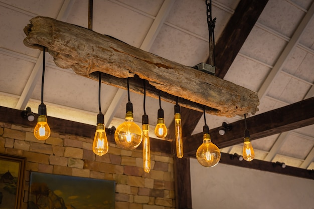 Lâmpadas incandescentes decorativas com madeira e contra o fundo da parede de tijolo