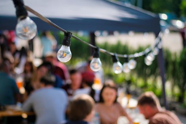 Lâmpadas penduradas em restaurante ao ar livre com vários visitantes ao fundo, churrasco