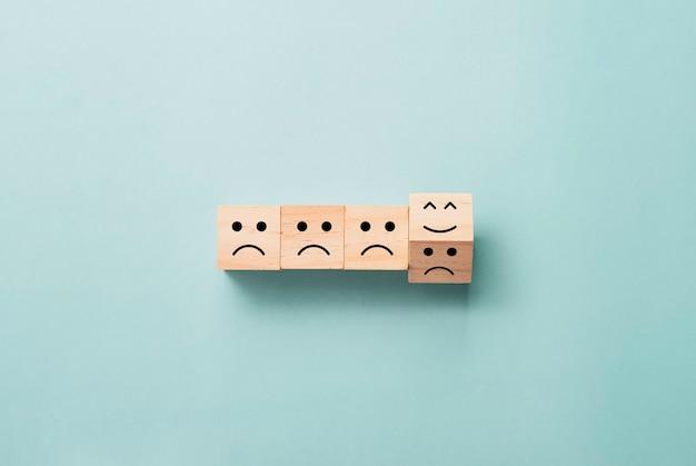 Lançando do bloco de cubos de madeira de triste para sorrir emoção no azul.