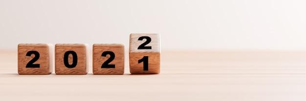 Lançando do bloco de cubos de madeira para mudar o ano de 2021 a 2022 na mesa de madeira e copiar o espaço para a preparação de feliz natal e feliz ano novo em 3d render.