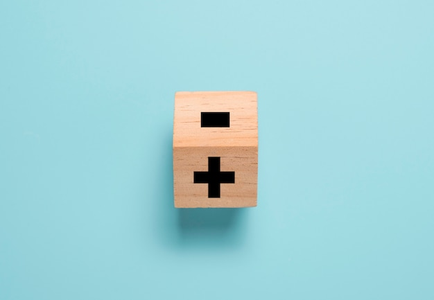 Lançando o bloco de cubo de madeira para alterar o sinal de menos para o sinal de mais na mesa azul. pensamento positivo e conceito de mentalidade.