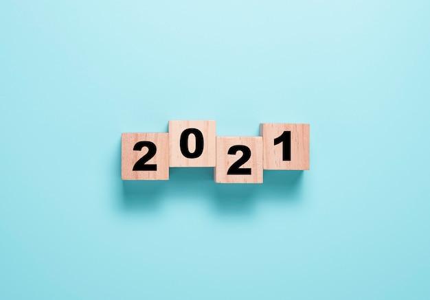 Lançando o bloco de cubos de madeira para a mudança de 2020 a 2021. feliz ano novo para iniciar um novo projeto e conceito de negócio.