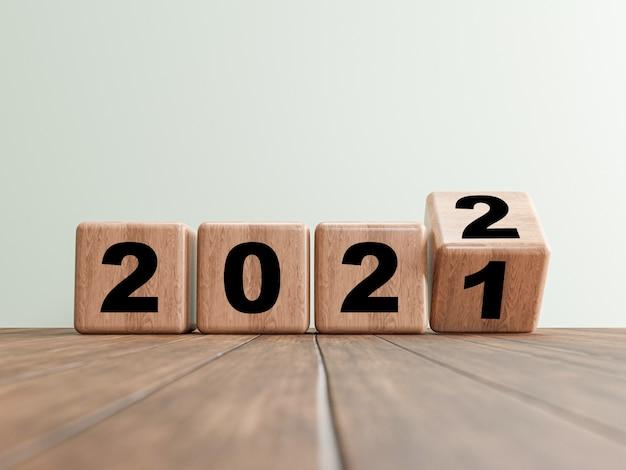 Lançando o bloco de cubos de madeira para a mudança de 2021 a 2022 no piso de madeira para a preparação de feliz natal e feliz ano novo, renderização em 3d