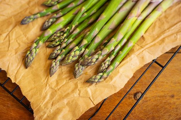 Lanças de espargos verdes frescos embrulhados em papel artesanal marrom para cozinha vegetariana saudável deitada em uma superfície de madeira, vista superior. fechar-se.