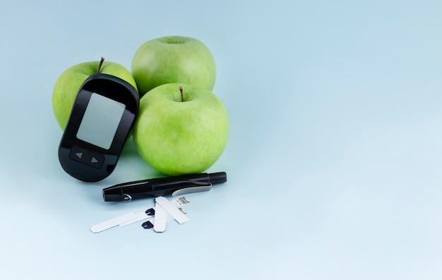 Lancelet medidor de glicose e maçãs verdes. dieta para diabéticos e conceito de vida saudável
