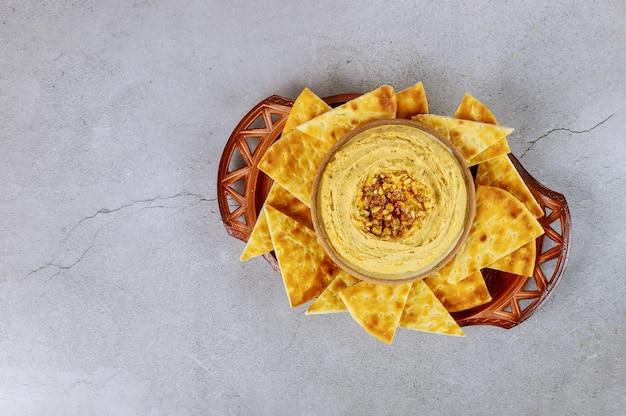 Lanche árabe com molho de hummus, fatias de pão pita no prato