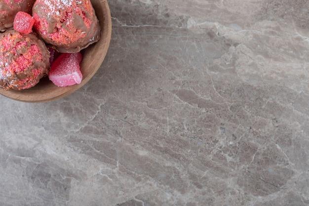 Lanche bolos e marmeladas em uma tigela pequena na superfície de mármore