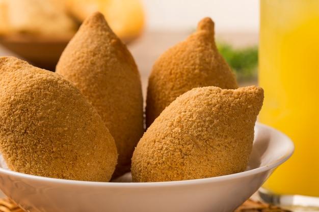 Lanche brasileiro de frango frito, popular em festas locais.