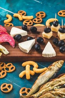 Lanche com fatias de linguiça, cubos de queijo e azeitonas pretas com bolachas e peixe seco