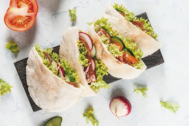 Lanche. comida para viagem, fast food de rua. sanduíche de pão pita com legumes frescos alface, pepino, tomate, rabanete, carne de bovino