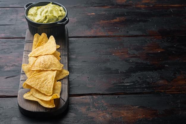 Lanche crocante mexicano, nachos chips e molho de abacate com guacamole de queijo, em mesa de madeira velha