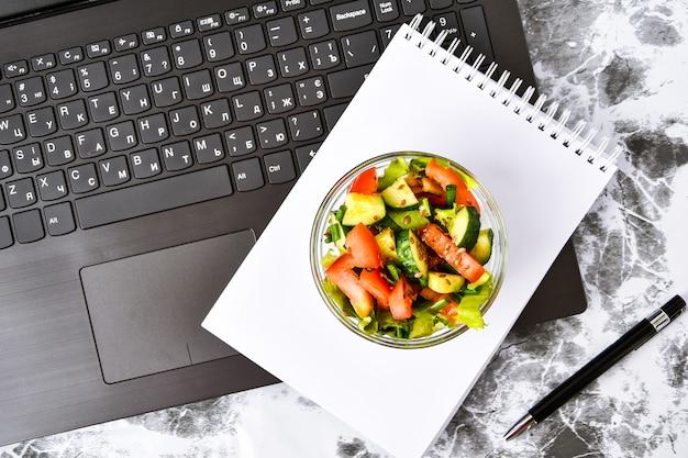 Lanche de almoço de negócios saudável no escritório, salada de legumes, caderno vazio com caneta