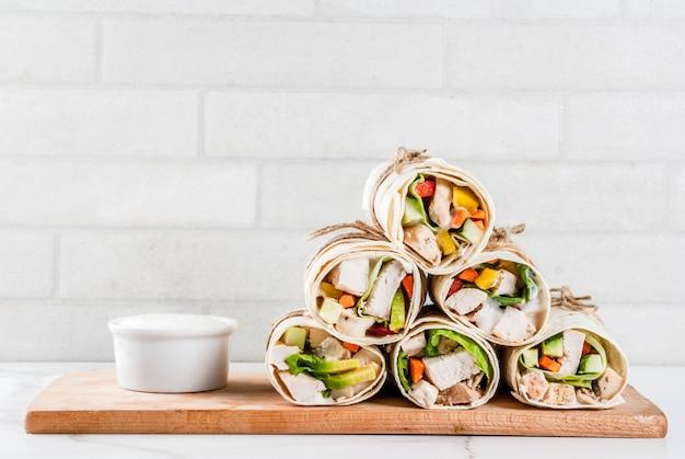 Lanche de almoço saudável. pilha de tortilla de fajita de comida de rua mexicana envolve com filé de frango grelhado de búfalo e legumes frescos