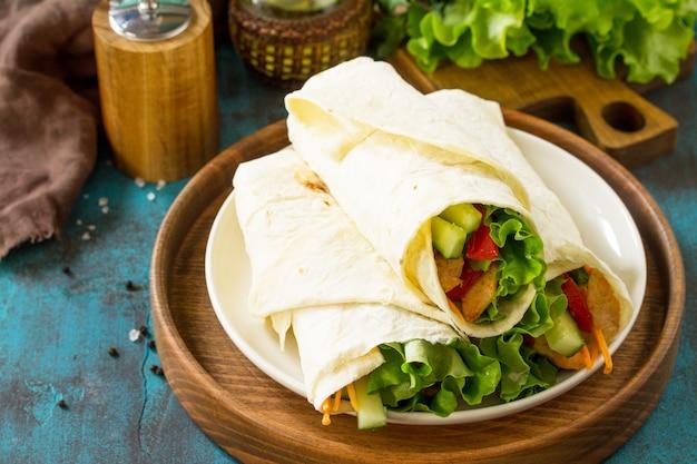 Lanche de almoço saudável tortilla embrulhada com frango grelhado e legumes frescos na mesa azul