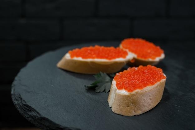 Lanche de baguete branca com caviar vermelho e manteiga com folhas de salsa em uma mesa contra um fundo preto em um restaurante. petisco chique dietético. excelente adição ao jantar.