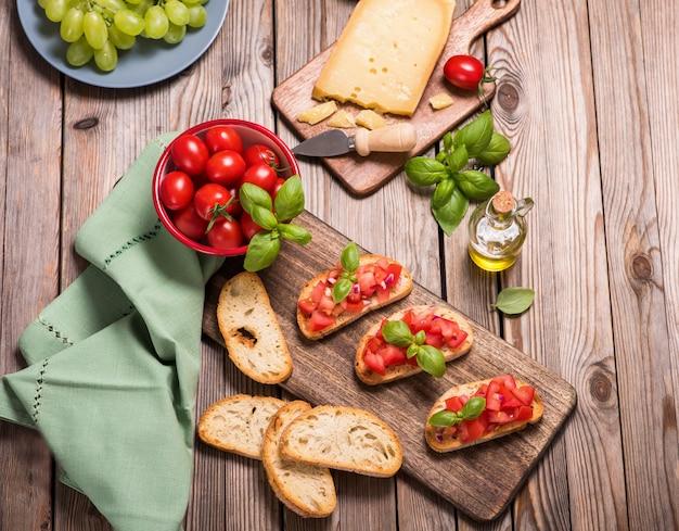 Lanche de bruschetta fresco na mesa de madeira com tomate, queijo e pão assado, aperitivo saudável lanche