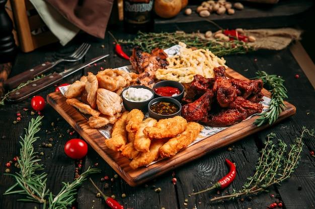 Lanche de cerveja com pedaços de peito de frango, asas, queijo e peixe com molhos na placa de madeira sobre o fundo preto de madeira