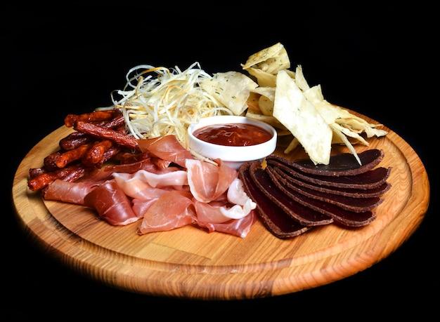 Lanche de cerveja em uma placa de madeira. basturma, carne seca, lulas secas, batatas fritas isoladas em um fundo preto.