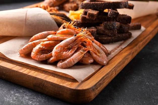 Lanche de cerveja, em uma placa de madeira. camarão. peixe frito. amendoim frito. fritas. asas de frango. croutons.