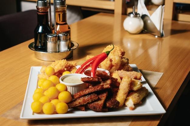Lanche de cerveja, torradas com alho, pão preto, nhoque, camarão em massa em um prato branco.