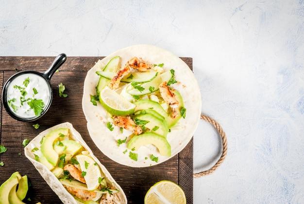 Lanche de comida saudável. taco de tortilhas com frango grelhado, abacate, salsa fresca, alface, limão