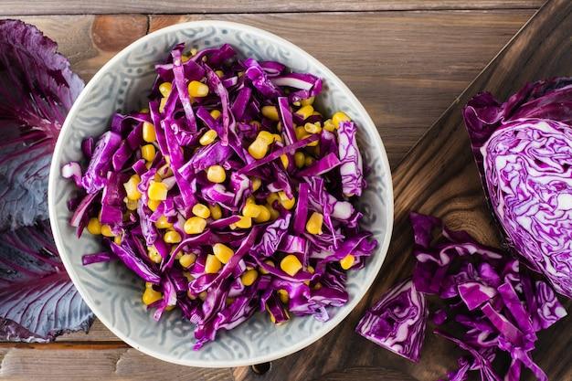 Lanche de dieta. salada de repolho roxo com grãos de milho em um prato sobre uma mesa de madeira