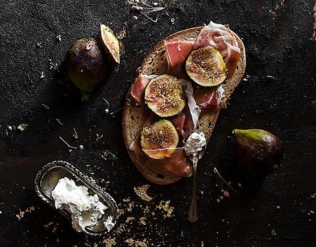 Lanche de verão com presunto de parma, figo e queijo fresco sobre pão de centeio