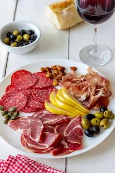 Lanche de vinho. presunto, presunto de parma, salame, amêndoas, azeitonas, baguete. antipasti.