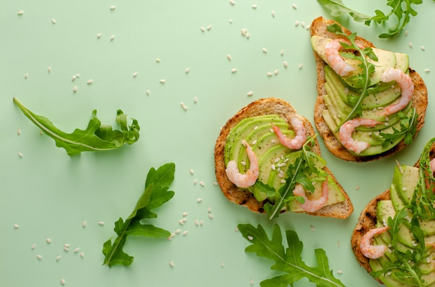 Lanche delicioso e saudável. torradas com abacate, camarão e rúcula sobre fundo verde pastel. vista superior, configuração plana,
