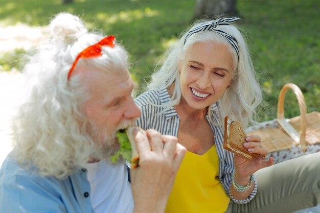 Lanche delicioso. mulher simpática e encantada segurando um sanduíche enquanto olha para o marido