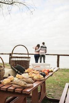 Lanche e frutas na mesa de piquenique com casal no fundo com vista para o mar