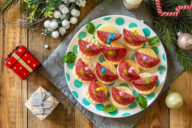 Lanche festivo de canapés na mesa de natal canapés com pão e queijo salame vista superior