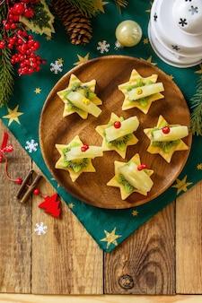 Lanche festivo de canapés na mesa de natal canapés de frutas com kiwi de queijo vista superior