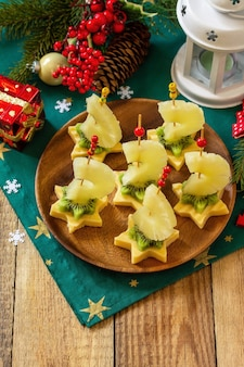 Lanche festivo de canapés na mesa de natal canapés de frutas com queijo kiwi copie o espaço