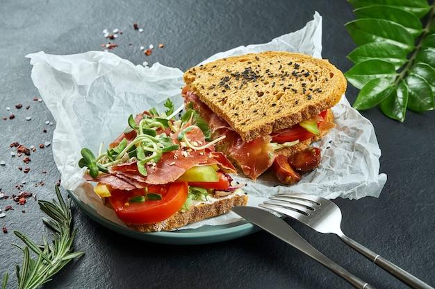 Lanche na rua na moda. saboroso sanduíche com jamon, tomate, pepino e microgreen em papel ofício em uma superfície preta