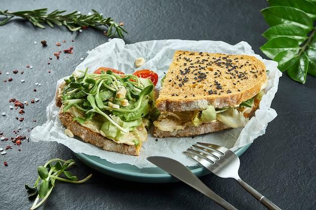 Lanche na rua na moda. torrada saborosa sanduíche com abacate e hummus e microgreen em papel ofício em uma superfície de ardósia preta
