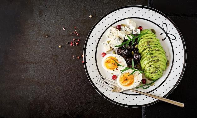Lanche ou pequeno-almoço saudável - prato de queijo azul, abacate, ovo cozido, azeitonas