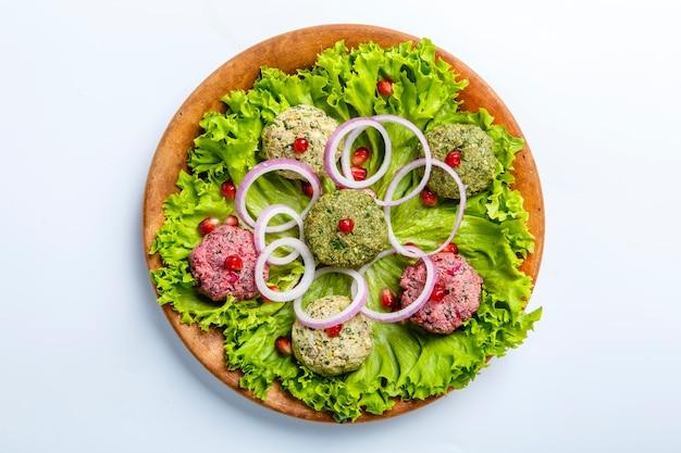 Lanche phali em forma de bolas coloridas à base de vegetais, espinafre, couve-flor e beterraba. o prato assemelha-se a um patê com molho de alho, nozes e lúpulo suneli.