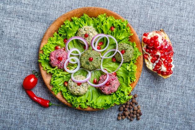 Lanche phali em forma de bolas coloridas à base de vegetais: espinafre, couve-flor e beterraba. o prato é semelhante a um patê com molho de alho, ervas, nozes e lúpulo suneli. em uma tela cinza