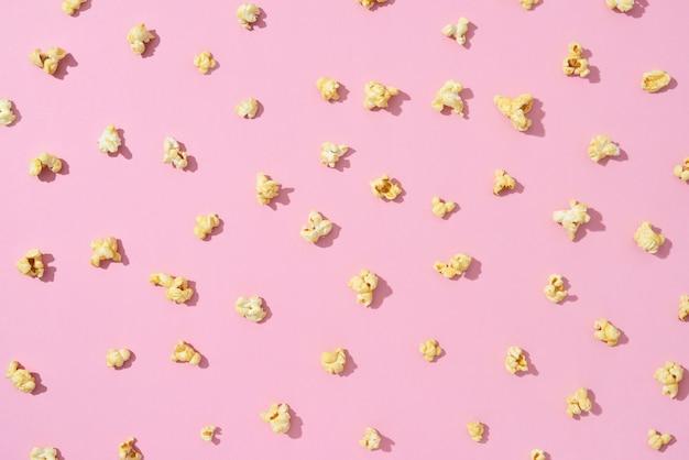 Lanche popular para diversão e assistir a filmes padrão de pipoca de sal ou sabor doce em uma parede rosa claro com sombras duras. postura plana.