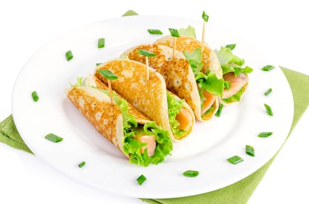 Lanche rola de panquecas, salmão e salada verde folhas.